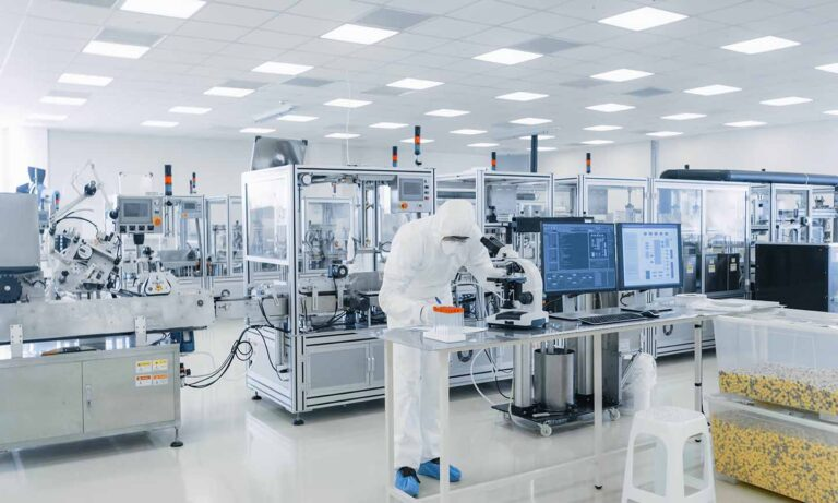 Shot of Sterile Pharmaceutical Manufacturing Laboratory where Scientists in Protective Coverall's Do Research, Quality Control and Work on the Discovery of new Medicine.