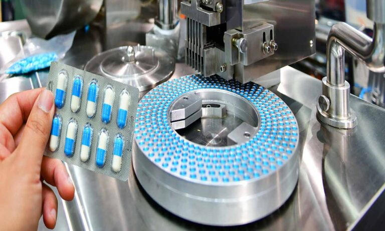 Hand holding blue capsule pack at medicine pill production line,
